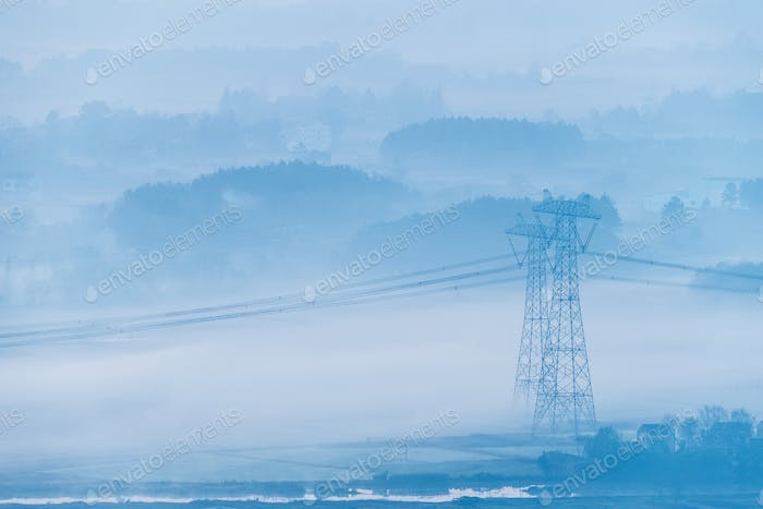power transmission towers in morning fog