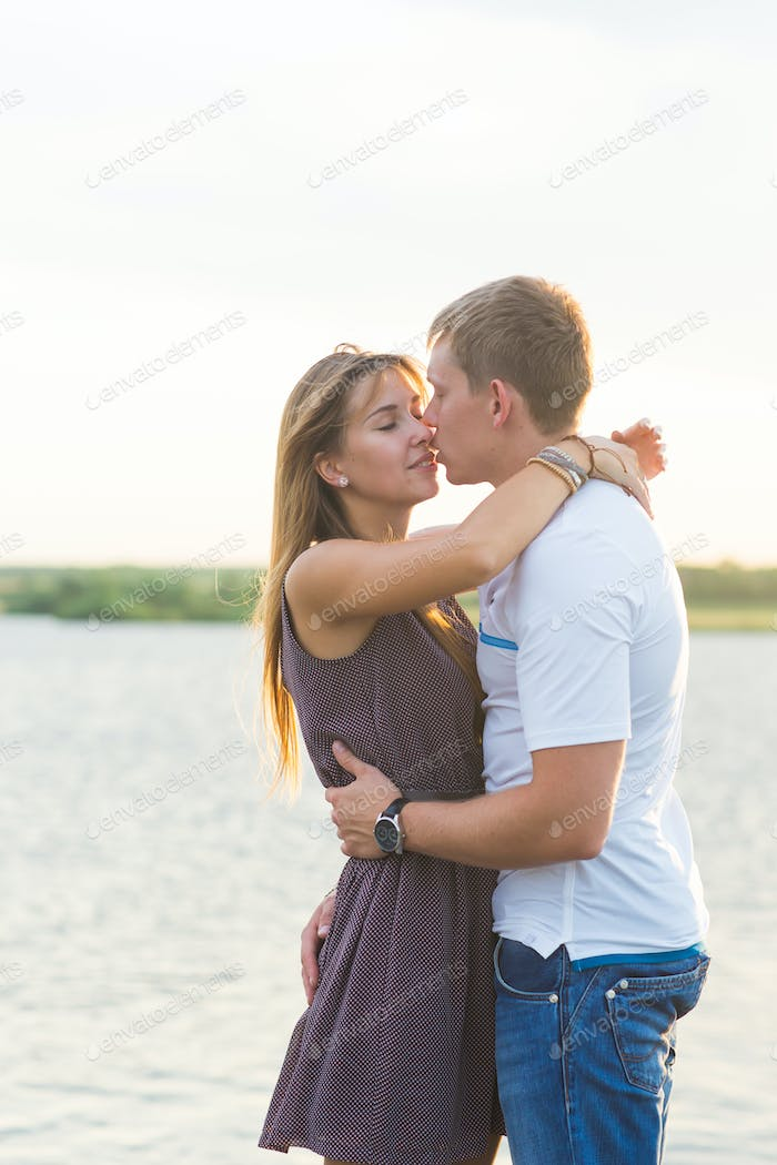 Young couple in love outdoors embracing together at lake