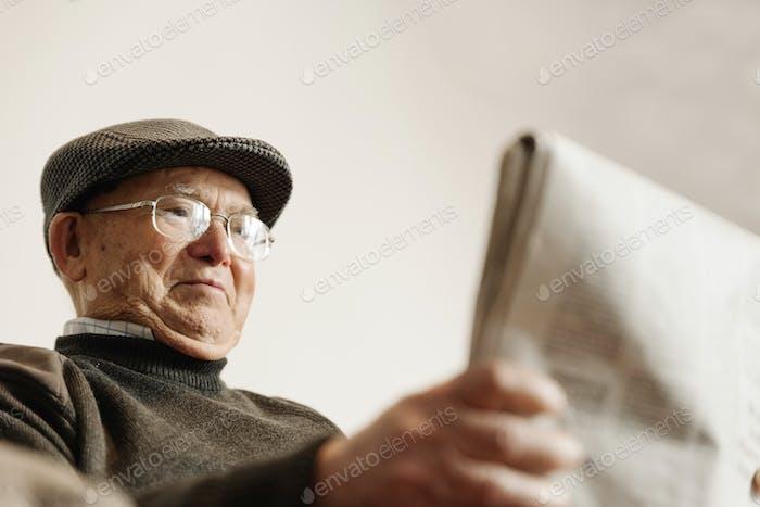 Älterer Mann liest eine Zeitung.