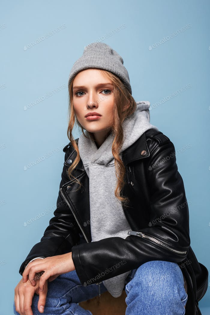 Young attractive serious woman in gray hat and black leather jacket thoughtfully looking in camera