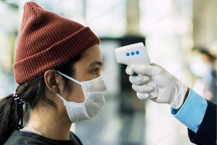 Woman in a medical mask getting her temperature measured by an electronic thermometer