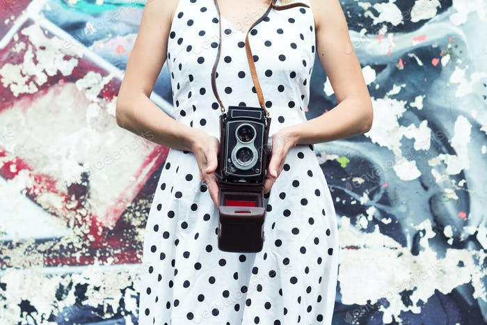 Close up of a woman in polka dress holding a camera