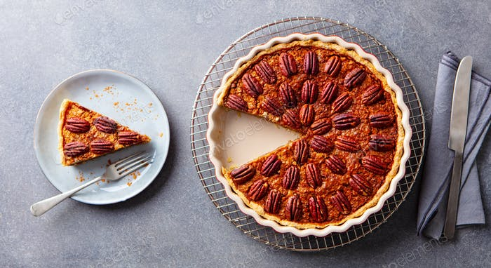 Pecan nuts pie, on a cooling rack. Grey background. Top view.