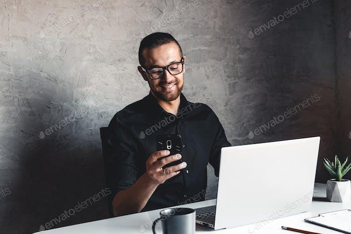 Ein maskierter Mann arbeitet am Computer. Pandemie, Coronavirus, Epidemie