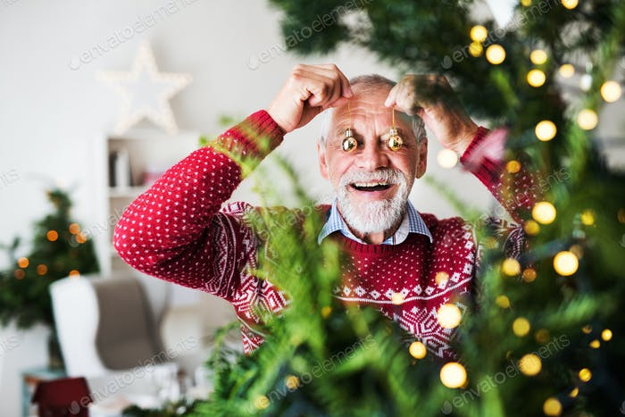 A senior man standing by Christmas tree, putting balls in front of eyes.
