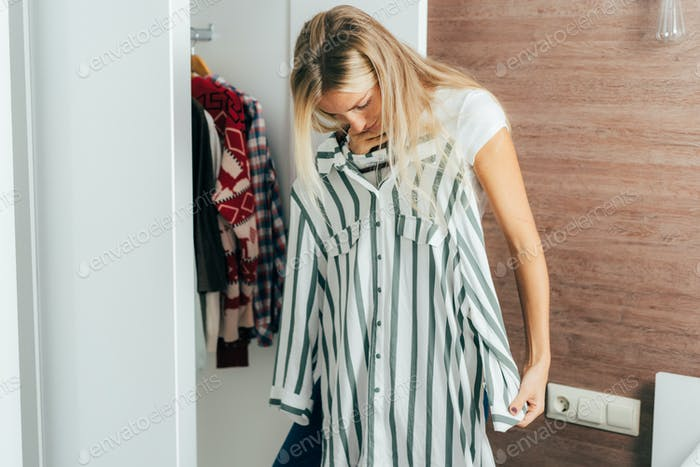 A woman chooses what to wear in her wardrobe, tries on different clothes.