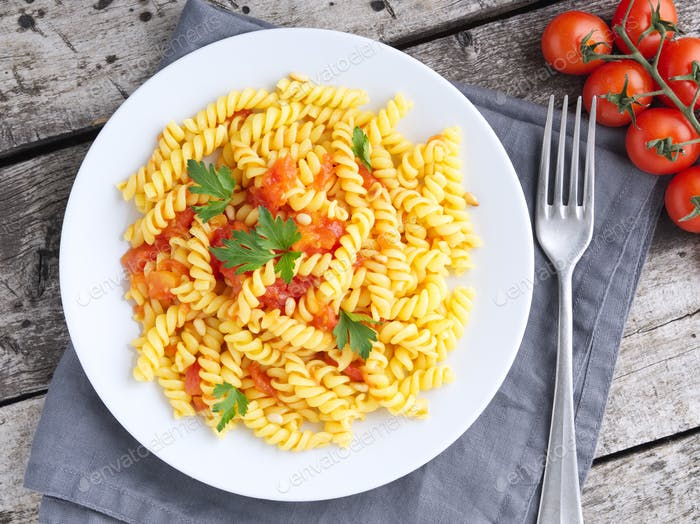 Pasta fusilli with tomatoes with parsley on a old rustic gray wooden background,