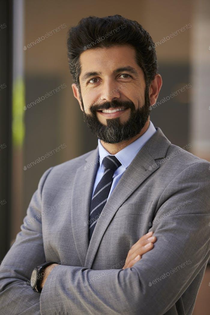 Smiling Hispanic businessman, arms crossed, close up vertical