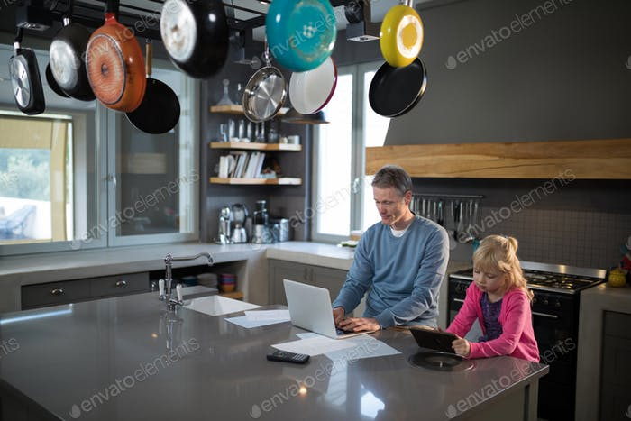 Father using a laptop while daughter is using a tablet