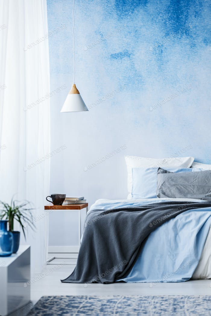 Blue and grey blanket on bed against ombre wall in bedroom inter