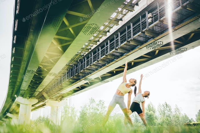 athletic women in sportswear do yoga exercises standing on lush green grass under railway overpass