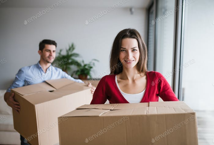 Young couple with cardboard boxes moving in a new home.