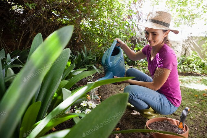 Smiling woman watering plants with can while crouching