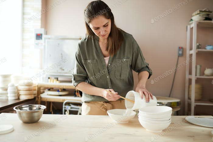 Female Potter Working in Shop