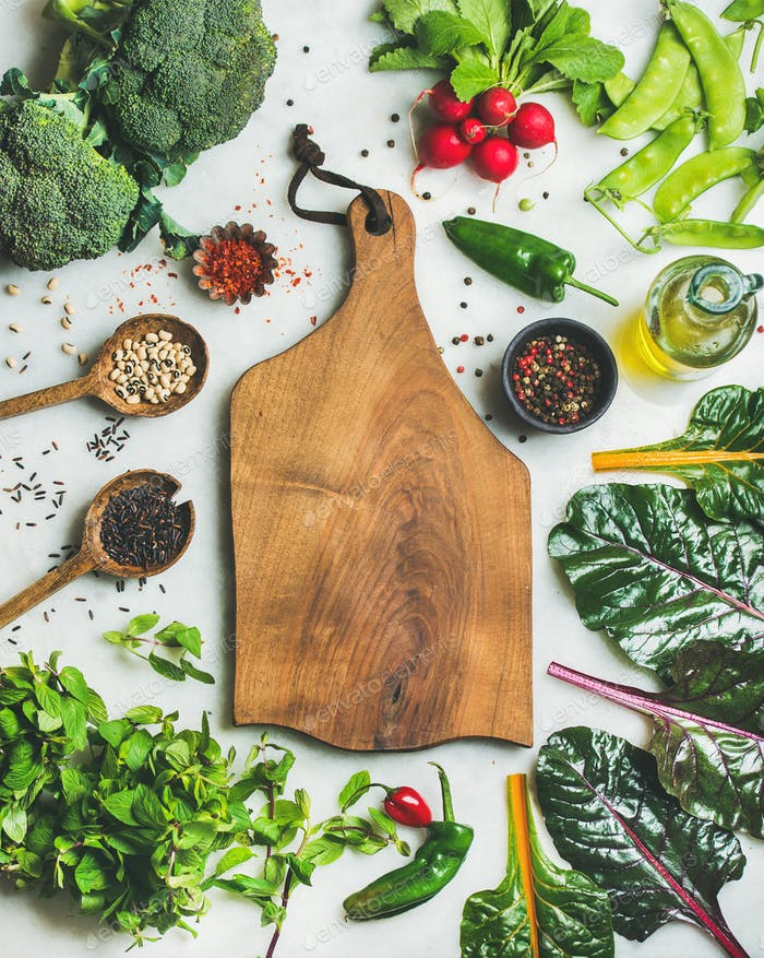 Fresh greens, raw vegetables and grains, wooden board in center