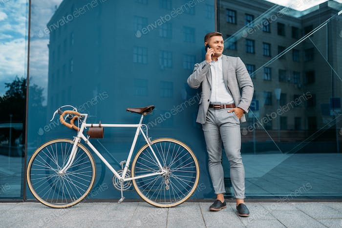Businessman talking by mobile phone at the bicycle
