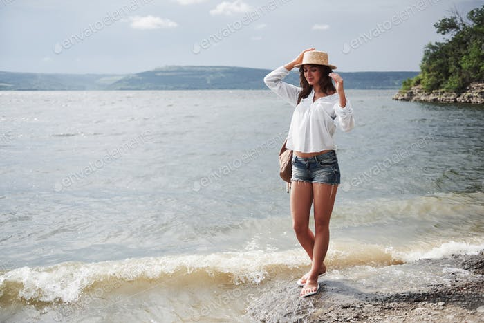 A beautiful young girl in a hat and with a backpack playfully walks by the water. A warm summer day
