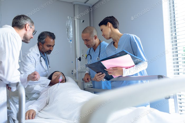 Caucasian male doctor adjusting oxygen mask while Asian female patient lying in  bed