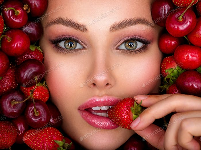 Young girl with bright makeup and a berry background. Beautiful caucasian woman biting a berry.