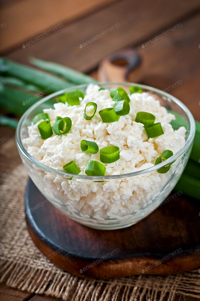 Useful cottage cheese with chives in a glass bowl on a wooden background