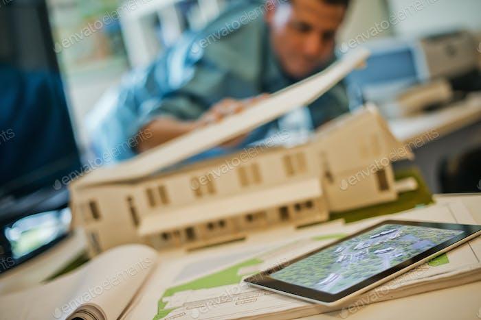 Architekten, die an einem Bauprojekt in einem Büro arbeiten. Ein Architektenmodell eines Hauses.