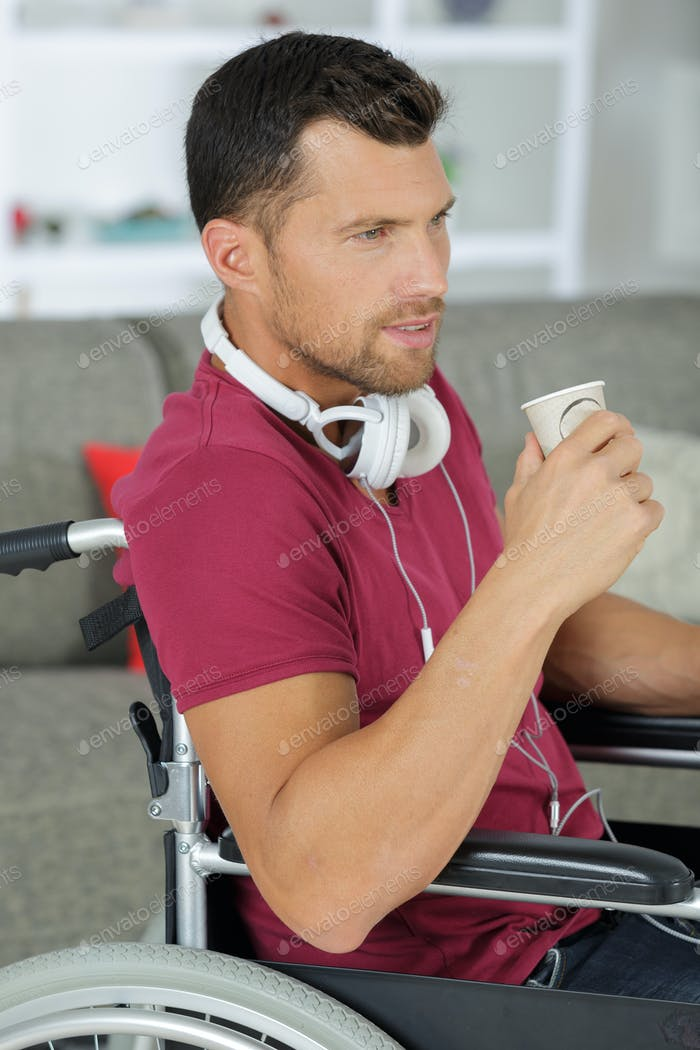 handsome man listening music on headphones while sitting in wheelchair