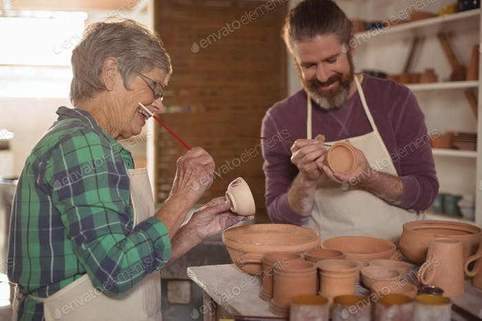 Male and female potter painting pots