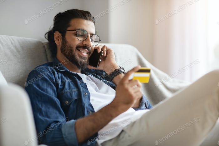 Online Banking. Handsome Western Guy Using Cellphone And Credit Card At Home