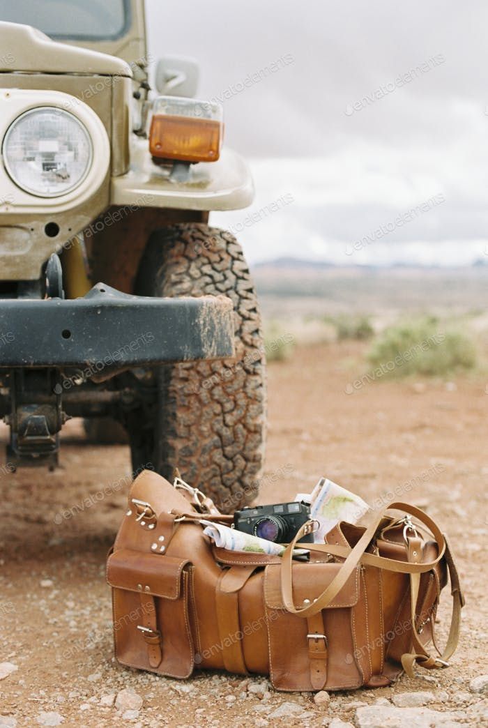 Leather overnight bag with a camera and map by a jeep wheel