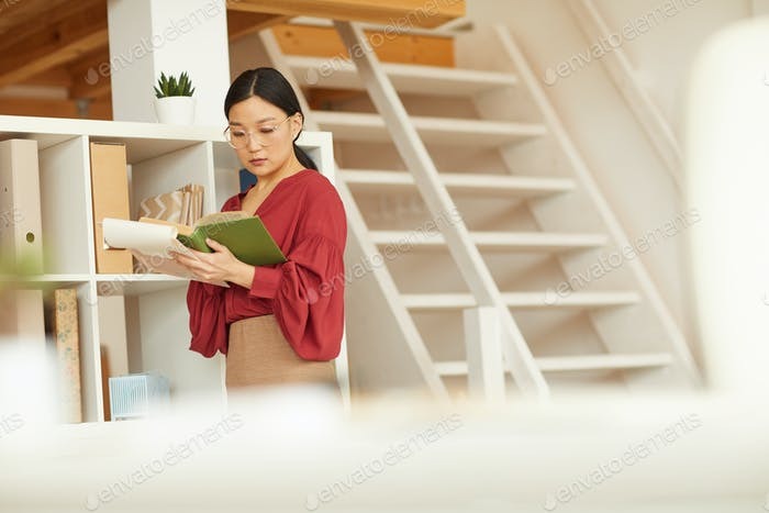 Erfolgreiche asiatische Geschäftsfrau Lesebuch