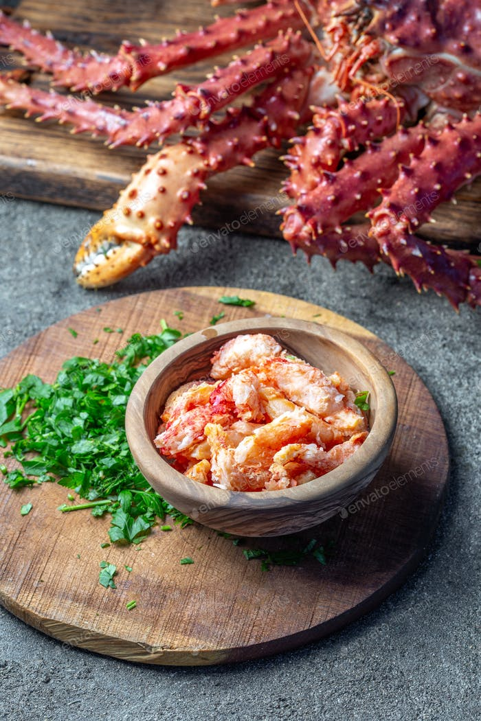 Crab meat of king crab in wooden bowl on gray background.