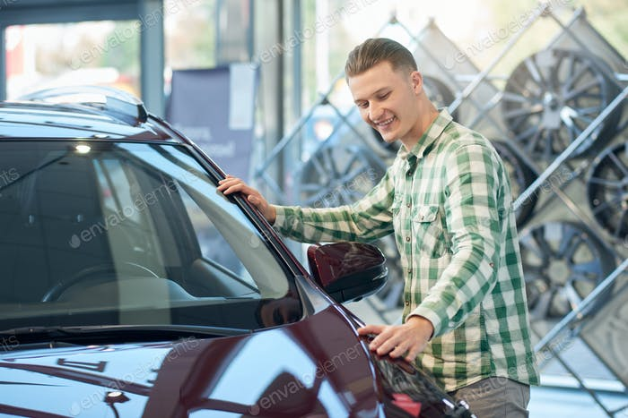 Smiling man checking car in dealership