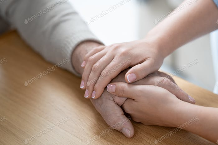 Hands of young affectionae and careful woman holding that of her senior father