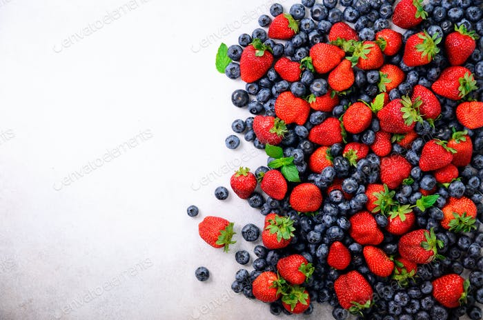 Assortment of strawberry, blueberry, currant, mint leaves. Summer berries background with copy space