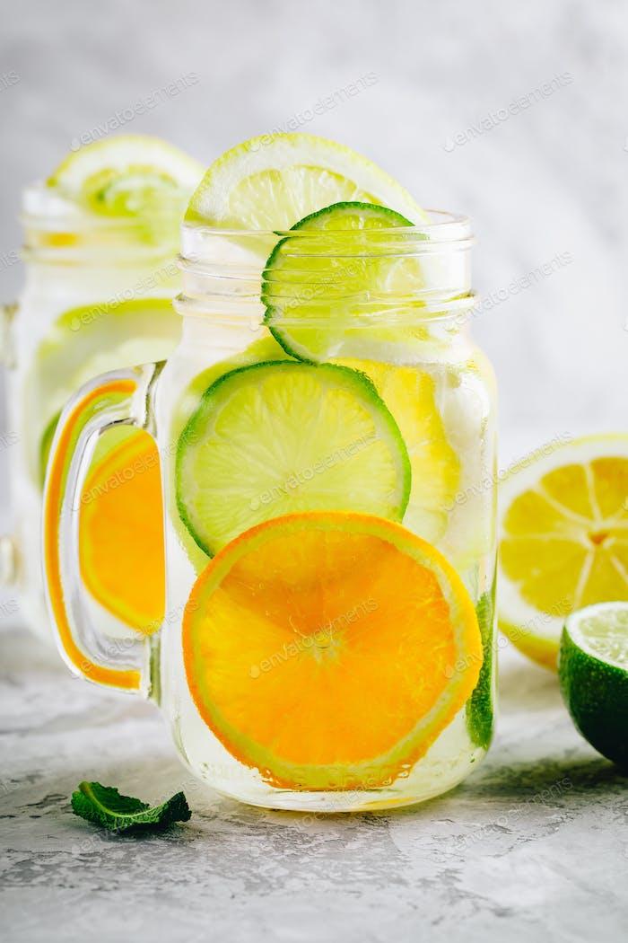 Infusion Detox Wasser mit Limette, Zitrone und Orangen Scheiben mit Minze.