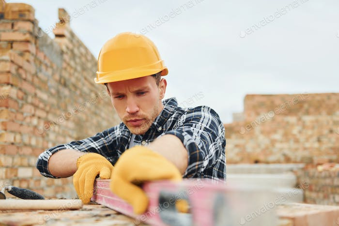 With level measuring tool. Construction worker in uniform and safety equipment have job on building