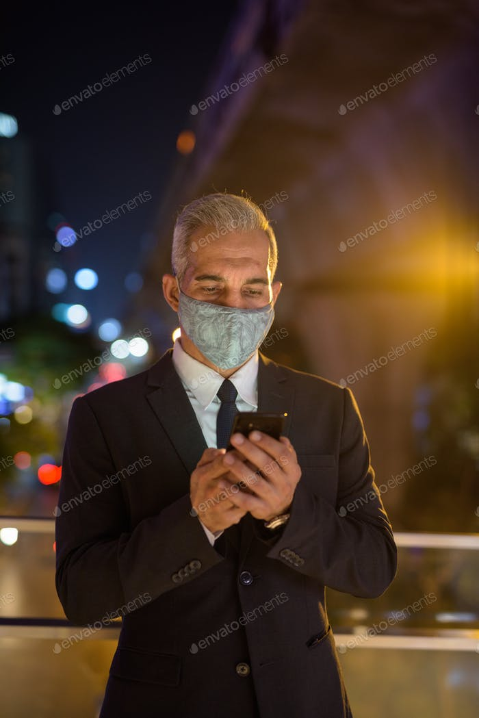 Businessman with protective facial mask in city at night using phone