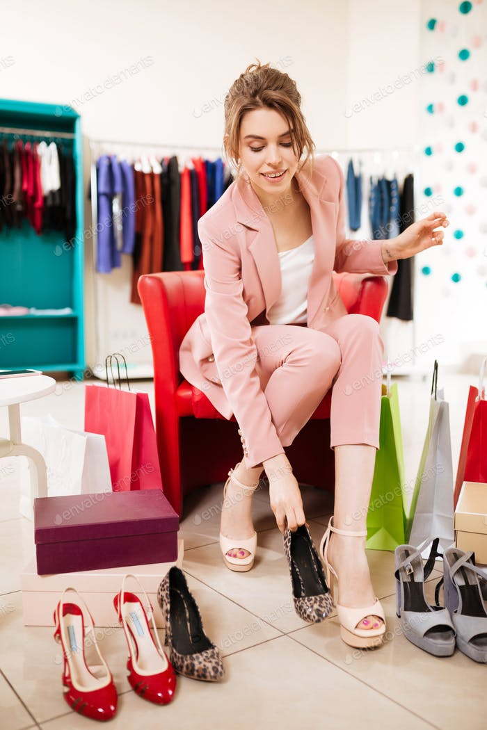 Girl in pink pantsuit sitting on chair and trying on shoes among clothes racks in fashion store