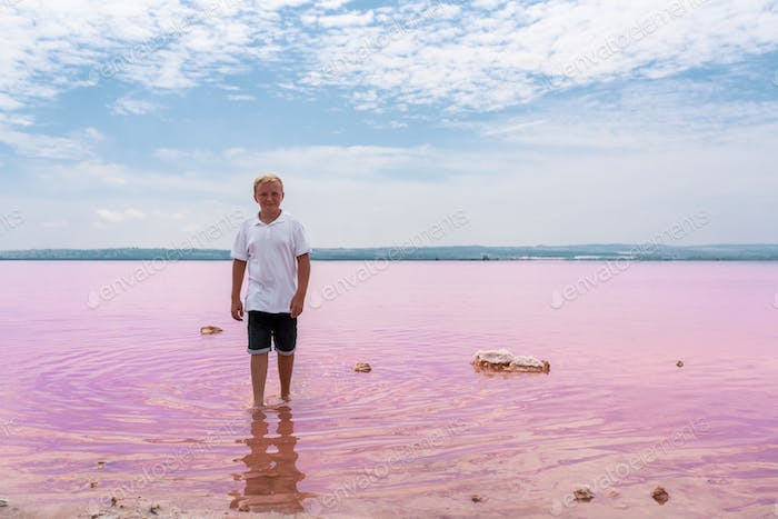 cute teenager boy wearing summer clothes on pink lake