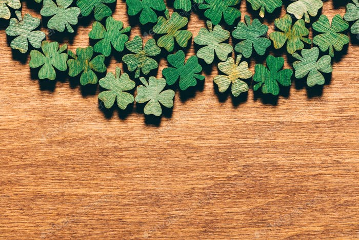 Wooden green shamrocks laying on the wooden floor.