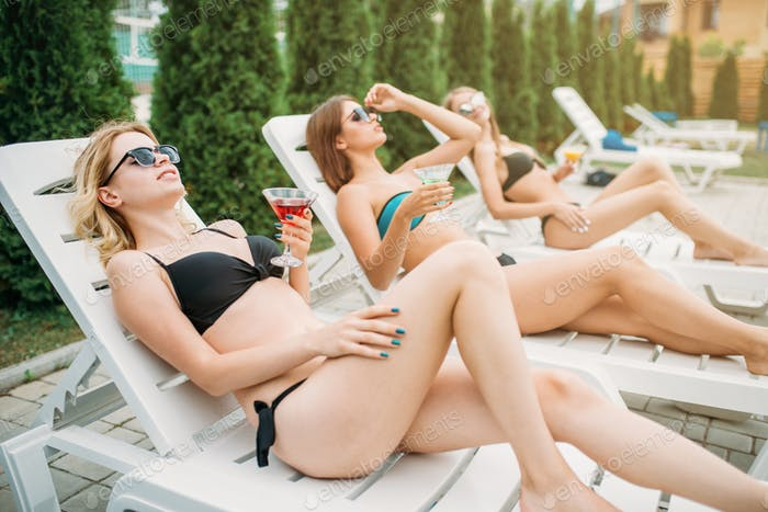 Three girls relax and sunbathig on deck chairs