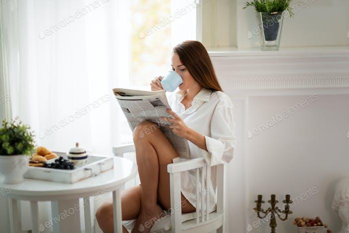 Friedliche junge Frau Lesemagazin zu Hause