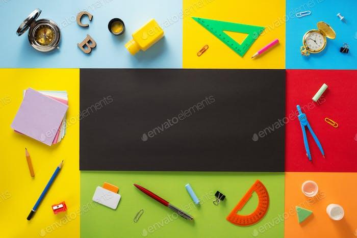 Schulbedarf auf abstraktem bunten Hintergrund