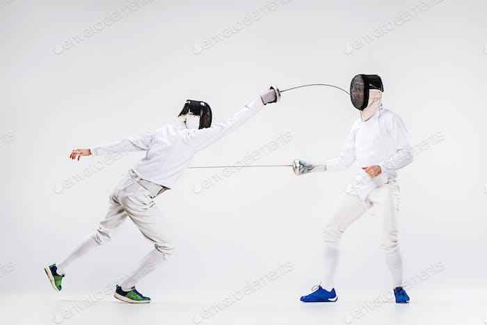 Die beiden Männer tragen Fechtanzug üben mit Schwert gegen grau