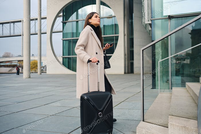 Side view of stylish businesswoman waiting on street with cellphone and suitcase