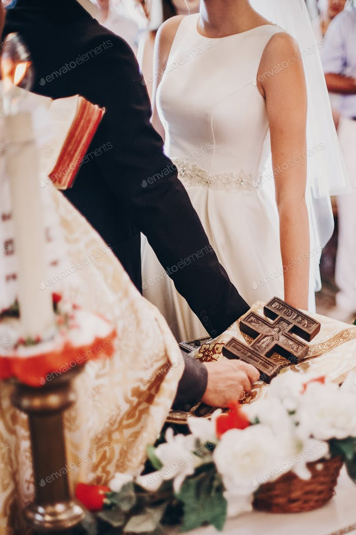 Wedding couple holding hands on altar under wooden cross
