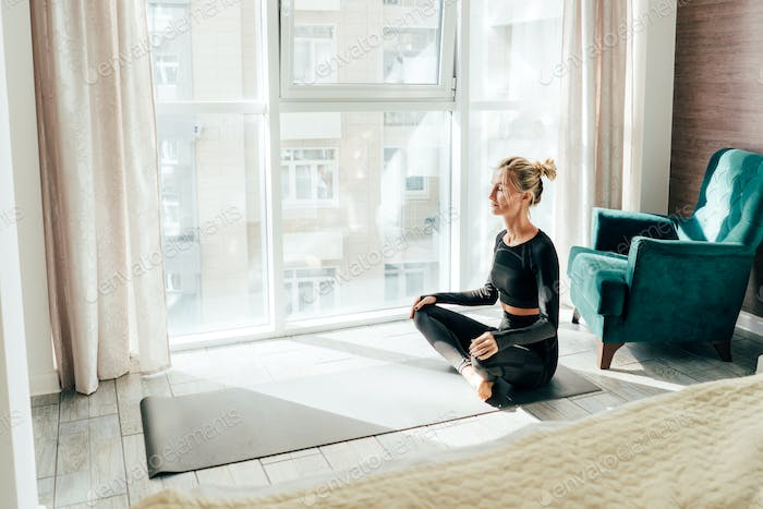 Woman sitting in lotus position on the floor in a light room meditates.