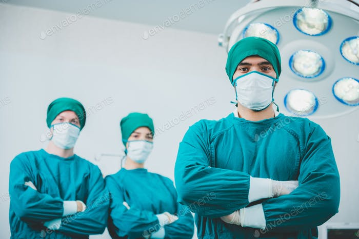 Portrait of male and female surgeon doctors wearing sterile gown with mask and gloves