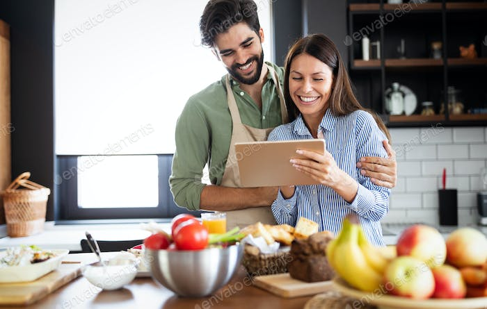 Beautiful couple in the kitchen while cooking