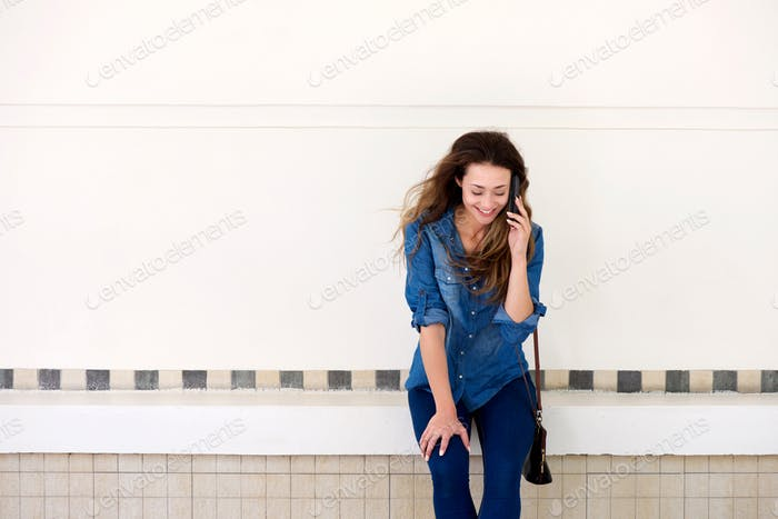 happy woman standing outside talking on mobile phone